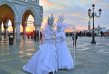 Disguised couple with Venetian masks at sunset, behind island of San Giorgio, carnival in Venice, Italy, Europe