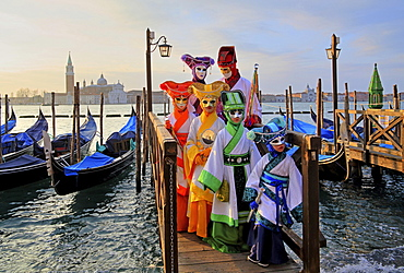Disguised persons with Venetian masks on walkway at the lagoon, behind island of San Giorgio, carnival in Venice, Italy, Europe