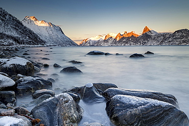 Norwegian fjord, snow-covered mountains at sunset, near Mefjordvær, Senja Island, Norway, Europe