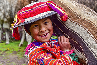 Indio Boy in traditional costume with poncho and hat, carrying bag, near Cusco, Andes, Peru, South America
