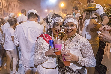 Two woman posing in front of crowd, white powder and white clothes, carnival La fiesta de los Indianos, Las Palmas de Gran Canaria, Canary Islands, Spain, Europe