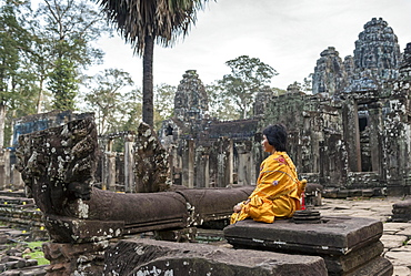 Woman meditates at Bayon Temple, Angkor Thom, Cambodia, Asia