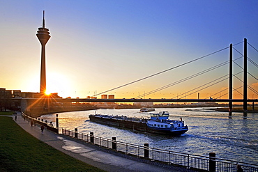 Rhine with cargo ship, Rhine Tower and Rheinkniebrücke, bridge at sunset, Düsseldorf, North Rhine-Westphalia, Germany, Europe