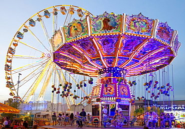 Illuminated swing carousel and Ferris wheel, Cranger Kirmes, the largest folk festival in the Ruhr district, Herne, North Rhine-Westphalia, Germany, Europe