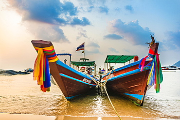 Moored colorful traditional long-tail boats on sandy beach, Ko Pha-ngan, Thailand, Asia