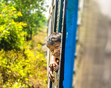 Small local boy looking out of moving train, Yangon Circular Railway, Yangon, Myanmar, Asia