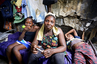 Woman, 40 years, and two children, 8 and 10 years, in barracks, Camp Icare for earthquake refugees, 5 years after the 2010 earthquake, Fort National, Port-au-Prince, Haiti, Central America
