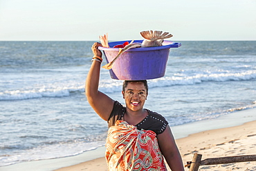 Malagasy woman carrying fish in a tub on her head, Morondava, Toliara province, Madagascar, Africa