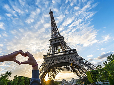 Hands forming heart, sunset behind Eiffel Tower, Paris, Ile-de-France, France, Europe