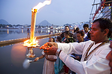 Brahmin conducting a religious ceremony, Aarti and Deepdan ceremony holding an oil lamp, sacred Pushkar Lake during the Pushkar Mela, Rajasthan, India, Asia