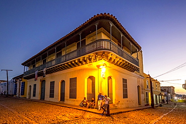 Residential house with adolescent Cubans outside, dusk, historic centre, Trinidad, Sancti Spiritus Province, Cuba, Central America