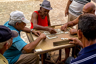 Cuban men playing dominoes at a table outside, old town,Trinidad, Sancti Spiritus Province, Cuba, Central America