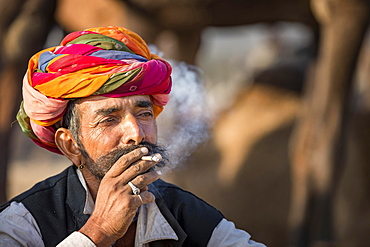 Portrait of Rajasthani man with turban smoking a cigarette, Pushkar, Rajasthan, India, Asia