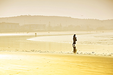 Rambler with a headscarf on the beach, silhouette in the morning light, Plage Tagharte, Essaouira, Morocco, Africa