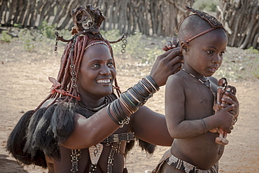 Ovahimba or Himba, a mother puts headdress on her son, Kunene district, Namibia, Africa