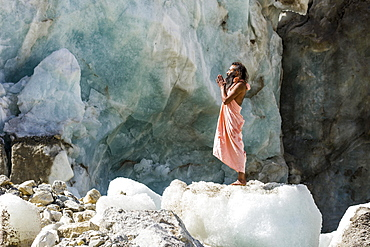 A Sadhu, holy man, is standing and praying on a block of ice at Gaumukh, the main source of the holy river Ganges, Gangotri, Uttarakhand, India, Asia