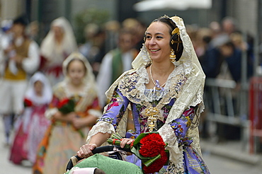 Fallas festival, young woman in a traditional costume during the parade in the Plaza de la Virgen de los Desamparados, Valencia, Spain, Europe