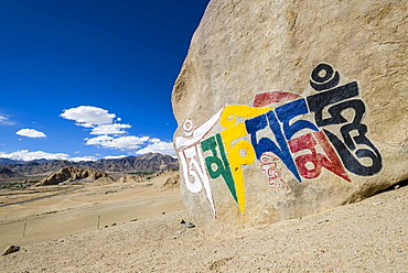 "A big Tibetan Mani Stone with the Mantra ""Om Mani Padme Hum"" colorfully engraved on a hill above the Indus Valley, Shey, Jammu and Kashmir, India, Asia"