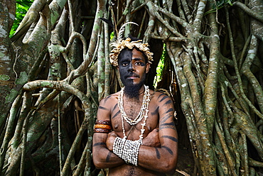 Tribal warrior in front of the roots of the banyan tree (Ficus benghalensis), Ekasup Cultural Village, Efate Island, Vanuatu, South Sea, Oceania