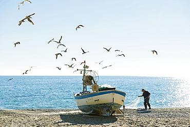 Fisherman with a fishing boat on the beach of Noli, Riviera di Ponente, Liguria, Italy, Europe