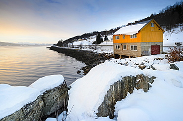 Winter atmosphere at sunrise on the fjord, snow-covered rocks at the front, typical Norwegian wooden house and coastal road, near Alesund, Norway, Europe