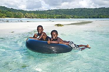 Two boys playing in the clear water, Espiritu Santo, Vanuatu, Oceania