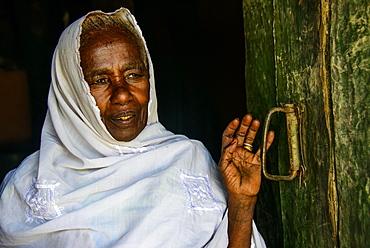 Friendly old woman standing in a door frame near Keren, Eritrea, Africa
