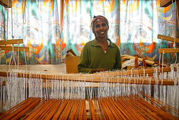 Friendly woman working on a hand weaving loom on social project, Eritrea, Africa