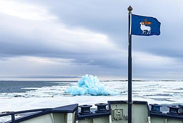 Flag of Gotland, Blue Iceberg drifting in Hinlopen Strait, Spitsbergen Island, Svalbard archipelago, Norway, Europe