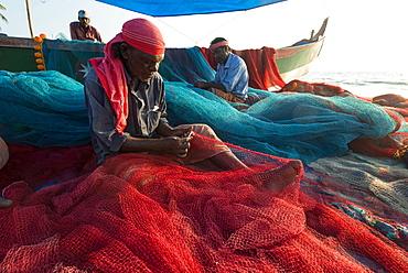 Fishermen repairing fishing nets on the beach, Varkala, Kerala, India, Asia
