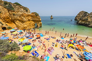 Tourists and bathers at the sandy beach, Praia do Camilo, Algarve rocky coast, Lagos, Portugal, Europe