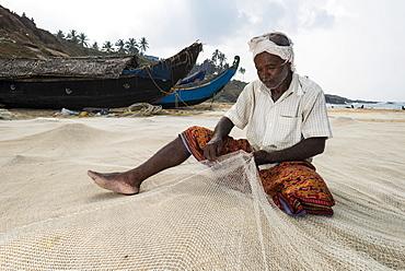 Fisherman repairing fishing nets on the beach, Vizhinjam, Kerala, India, Asia