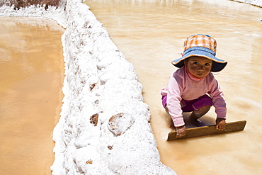 Child playing with a wooden board, Salinas de Maras salt pans, created by the Incas and still in operation, Pichingote, Cusco region, Andes, Peru, South America