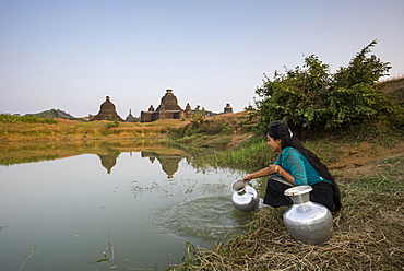 Smiling girl drawing water from a water hole with a vessel made of aluminium, Laymyetnta Pagoda or Temple, Mrauk U, Sittwe District, Rakhine State, Myanmar, Asia