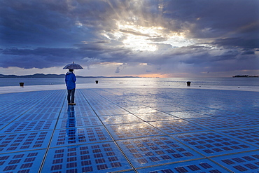 "Woman holding an umbrella, standing on the solar art installation """"Greeting to the Sun"""", Zadar, Dalmatia, Croatia, Europe"