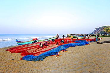 Fishermen repairing nets on the beach, Arabian Sea, Varkala, Kerala, South India, India, Asia