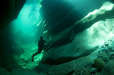Diver looking at traces of erosion on the riverbed of the Verzasca River, Lavertezzo, Valle Verzasca valley, Canton of Ticino, Switzerland, Europe