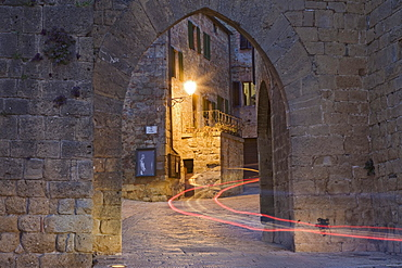 City gate with the light trace of a passing car, Monticchiello, Val d'Orcia region, Province of Siena, Tuscany, Italy, Europe