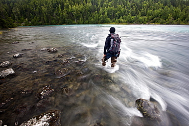 Man wearing fishing boots on the bank of Lowe River near Valdez, Alaska, USA, North America