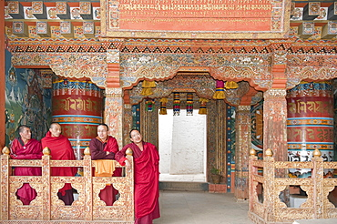 Four monks in red robes, ornate wooden wall, Buddhist Tango Goemba Monastery near Thimphu, Kingdom of Bhutan
