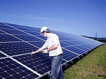 Solar installation technician checking solar panels with a measuring device