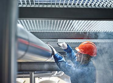 Technician, mechanic with orange helmet mounting a refrigeration line bracket, Austria, Europe