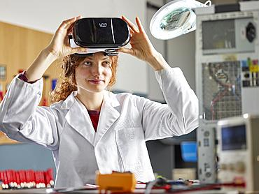 Engineer with white lab coat with VR goggles, Austria, Europe