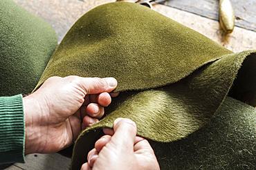 Hands checking different wool felt hat bodies, shades of green, on workbench, hatmaker workshop, Bad Aussee, Styria, Austria, Europe