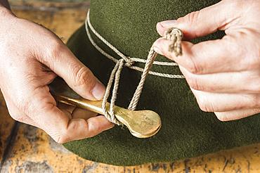 Tightening the shaping cord around a wool felt hat, using iron tool, hatmaker workshop, Bad Aussee, Styria, Austria, Europe