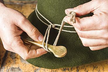 Tightening the shaping cord around a wool felt hat, using iron tool, hatmaker workshop, Bad Aussee, Styria, Austria, Europe
