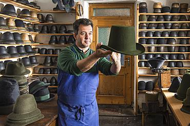 Hatter examining finished wool felt hat, hat molds on wooden shelves and finished hats behind, hatmaker workshop, Bad Aussee, Styria, Austria, Europe