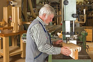 Wooden mask carver cutting a wooden block using a band saw, Bad Aussee, Styria, Austria, Europe