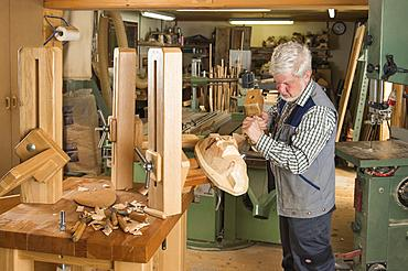 Wooden mask carver using wood carving tools on a wooden block, wooden mask carver, workbench, Bad Aussee, Styria, Austria, Europe