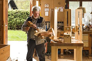 Wooden mask carver using wood carving tools at workbench in workshop, Bad Aussee, Styria, Austria, Europe